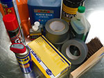 A photo of some tape, WD40 and other bits
